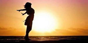 להיות חופשי, צללית של אישה פורסת ידיים על רקע השקיעה