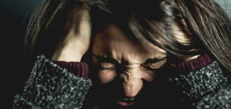 טיפול בחרדות קשות, אישה לחוצה מחזיקה את הראש עם הידיים